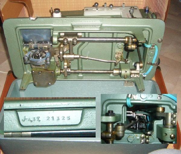 Unterseite der grünen Nähmaschine, mit eingeblendeter Seriennummer und Blick oben in den Arm